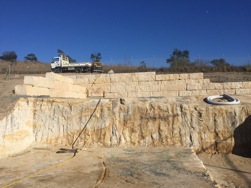 Excavation with sandstone boulder retain walls